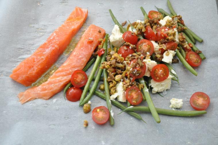 Gör så här Antingen så använder du allt fryst, eller så tinar du bönorna och låter dem rinna av. Jag tyckte nog att det blev bäst med tinade, något avrunna bönor. Så vi kör på det. Men har du bråttom så går det jättebra med frysta. Sätt ugnen på 225 C Lägg ett bakplåtspapper på en ugnsplåt. Häll på bönorna, fetaosten i kuber, tomaterna i halvor och oliver. Lägg laxen på bakplåtspappret bredvid bönhögen. Ringla över rikligt med olivolja, pressa saften ur citronhalvan och strö över flingsalt. Jag tog lite rökt paprikapulver över laxen också. Skjuts in i ugnen i sådär 15-20 minuter (om laxen är fryst).